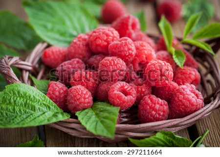 Fresh organic ripe raspberry with leaf in basket,  selective focus - stock photo