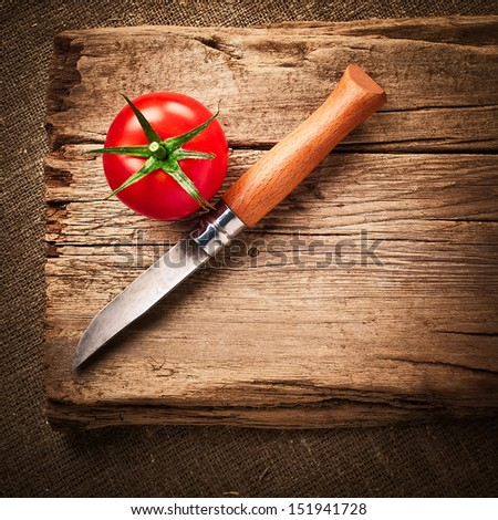 Fresh organic ripe tomato and steel knife on wooden table. Image in vintage style - stock photo