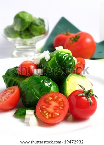 Fresh organic salad of Brussels sprouts and cherry tomatoes, on white dish