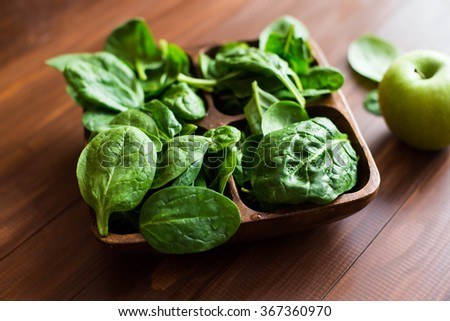 Fresh, organic spinach in a bowl on rustic wooden background.