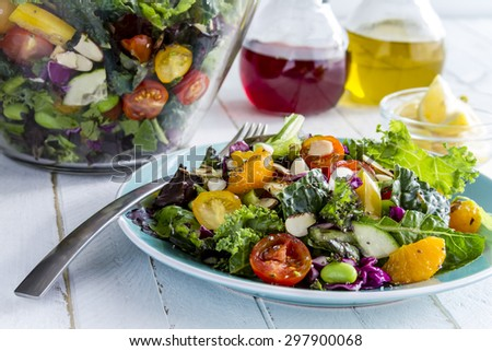 Fresh organic super food salad sitting on blue plate with fork on side and olive oil, red wine vinegar and lemons in background - stock photo