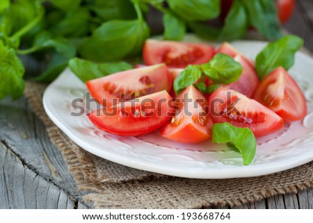 Fresh organic tomatoes and basil on the wooden table, selective focus