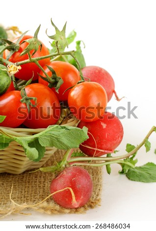 Fresh organic tomatoes and cucumbers in a basket on a white background - stock photo