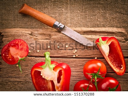 Fresh organic tomatoes, paprika, steel knife and wooden cutting board on canvas tablecloth. Image in vintage style - stock photo