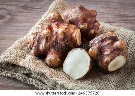 Fresh organic topinambur on wooden background - stock photo