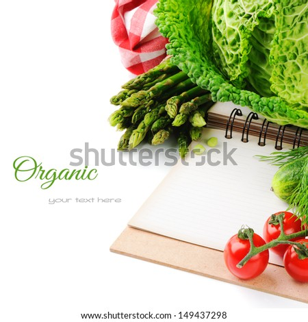 Fresh organic vegetables and cooking book isolated over white - stock photo