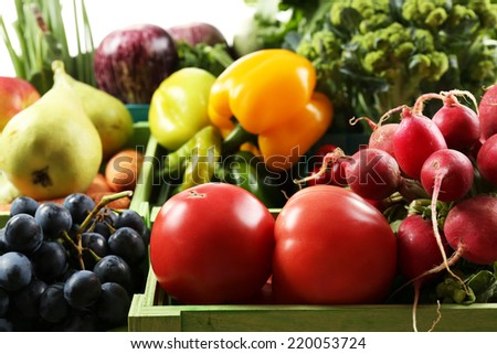 Fresh organic vegetables and fruits in wooden boxes, close up - stock photo