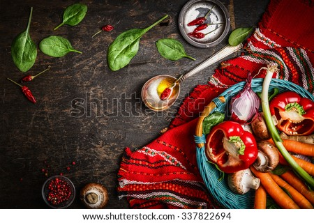 Fresh organic vegetables and seasoning ingredients in basket on rustic kitchen table with spoon and oil. Healthy food or vegetarian food concept. - stock photo