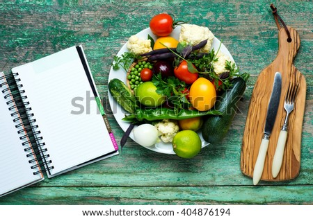Fresh Organic Vegetables on a White Plate with Knife and Fork.   Vertical Composition.  - stock photo