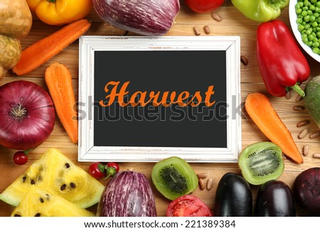 Fresh organic vegetables with chalkboard on wooden table, close up - stock photo