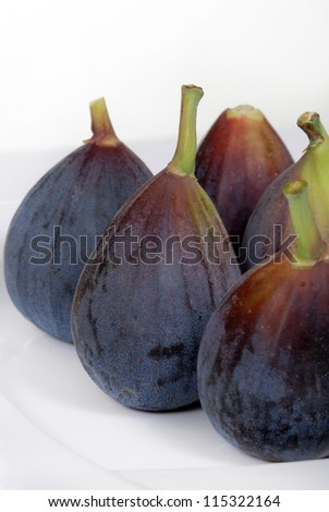 Fresh, organic, whole, purple figs on a white plate.  Shallow depth of field. - stock photo