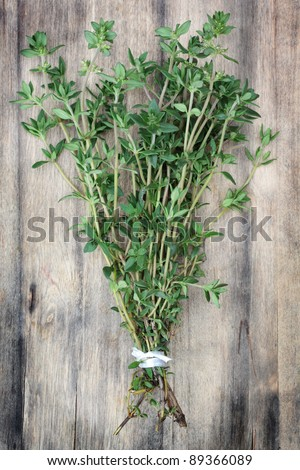 Fresh, organically grown thyme on an old wooden chopping board.