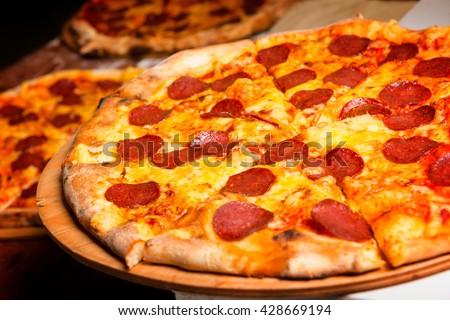 Fresh original Italian pizza on a wooden board in Italian pizzeria - stock photo