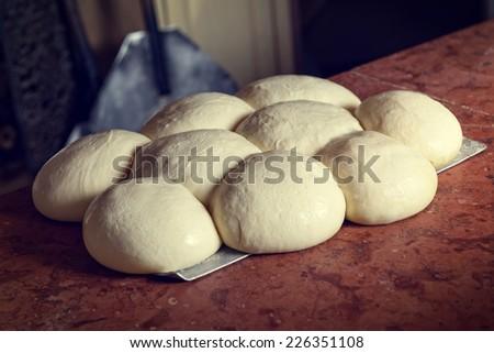 Fresh original Italian raw pizza dough, shovel and stone oven in background. - stock photo