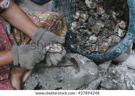 Fresh oyster held open with knife in hand  - stock photo