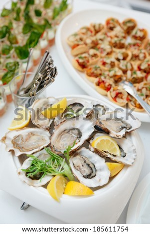 Fresh oysters and another dishes on restaurant table - stock photo