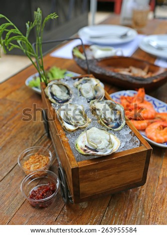 Fresh oysters with ice on a wooden desk - stock photo