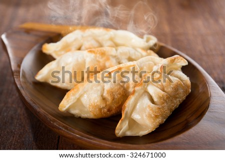 Fresh pan fried dumplings on plate with hot steams. Asian meal on rustic old vintage wooden background. - stock photo