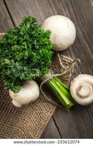 Fresh parsley with white mushrooms on burlap sack. On wooden table. - stock photo
