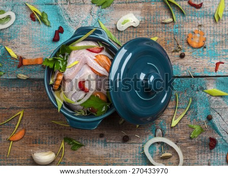 Fresh partridge in a pot with vegetables on old wooden table - stock photo