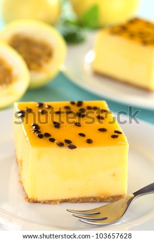 Fresh passion fruit cheesecake dessert on plate with pastry fork with another cake and yellow passion fruits in the back (Selective Focus, Focus on the left upper front edge of the cake) - stock photo