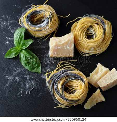 fresh pasta with ingredients on slate, background - stock photo