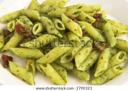 fresh pasta with pesto and sun dried tomatoes on a plate - stock photo