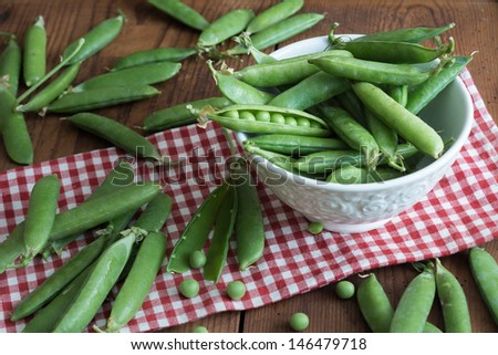 fresh Pea pods in a bowl on wooden Table - stock photo