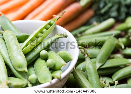 fresh Pea pods in a bowl with carrots - stock photo