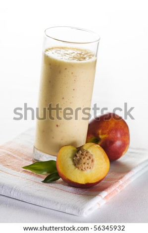Fresh peach smoothie in tall glass close up