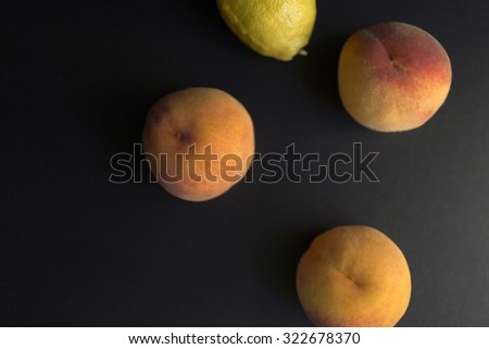Fresh peaches and a lemon on a black background, top view