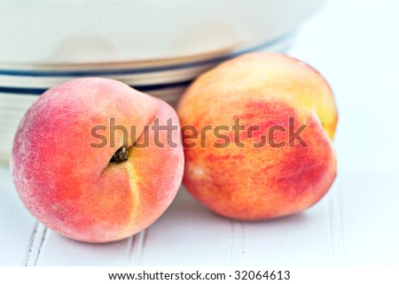 Fresh peaches by an antique bowl