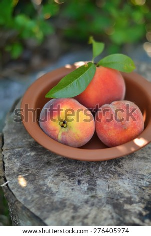 fresh peaches in a vintage bowl on a wooden surface - stock photo