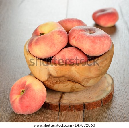 Fresh peaches in a wooden bowl on a brown table