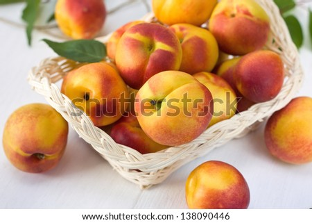 Fresh Peaches (Nectarine) in a basket on a wooden board