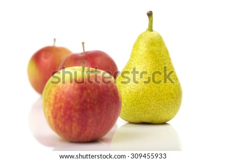 Fresh pear among red apples isolated on white