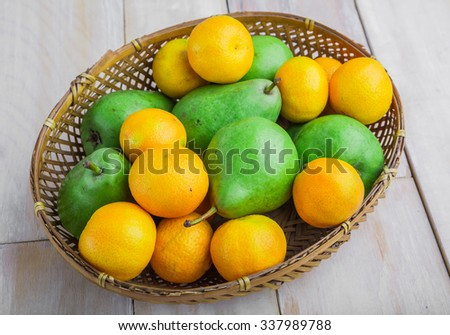 Fresh pears and tangerines in wicker basket on white table - stock photo