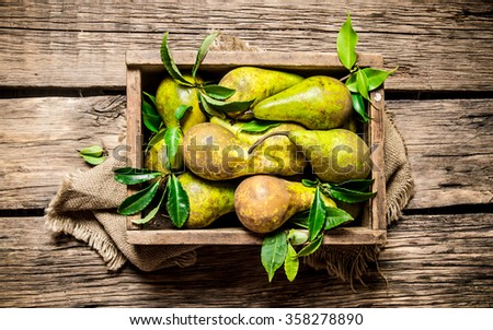 Fresh pears in an old box with leaves. On wooden background. Top view - stock photo