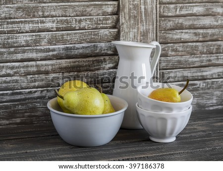 Fresh pears in bowl and vintage crockery on a dark wooden background. Kitchen still life in rustic style - stock photo