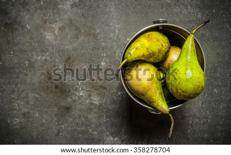 Fresh pears in the bucket. On the stone table. Free space for text . Top view - stock photo