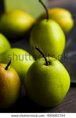 Fresh pears on a rustic wooden background. Shallow depth of field. - stock photo