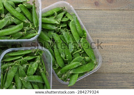 Fresh peas in a plastic container on a wooden background