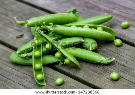 Fresh peas on a background of old boards - stock photo