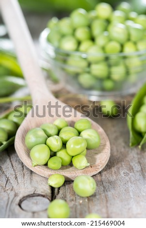 Fresh Peas on a cooking spoon (vintage wooden background) - stock photo