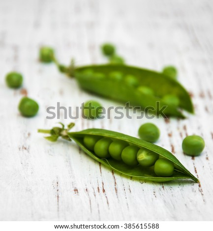 fresh peas on a wooden background - stock photo