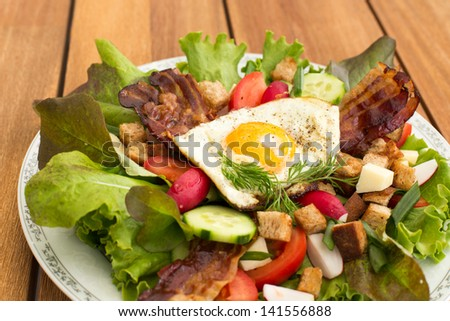 Fresh peasant salad also called country salad, greek salad or village salad. Composed with lettuce, cucumber, onion, radish, fried egg and bacon, cheese, tomatoes, parsley and croutons.