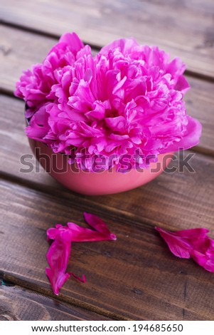 Fresh peony flower in bowl on wooden background. Selective focus, vertical. - stock photo