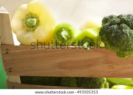 fresh pepper and broccoli in a wooden crate