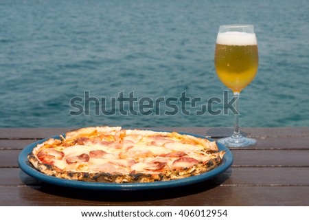 Fresh pepperoni pizza on a blue plate and glass of beer on wooden and water background - stock photo