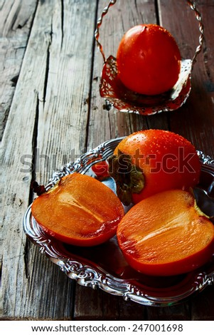 Fresh persimmon and cut persimmon on rustic wooden background. - stock photo